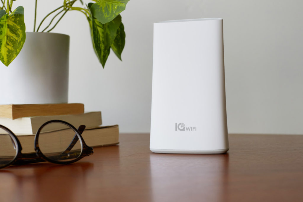 IQ Wi-Fi Router on table next to glasses, books, and a plant. Links to IQ WiFi Mesh Router Page.